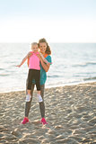 Healthy mother and baby girl having fun time on beach in the eve