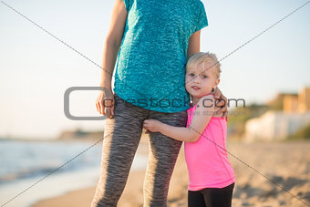 Baby girl hugging mother on beach in the evening