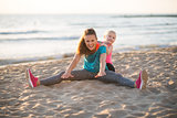 Healthy mother and baby girl stretching on beach in the evening