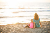 Healthy mother and baby girl sitting on beach in the evening. re
