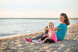 Healthy mother and baby girl sitting on beach in the evening