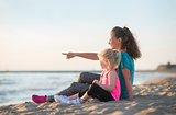 Baby girl and mother pointing while sitting on beach in the even