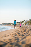 Healthy mother and baby girl running on beach in the evening. re