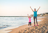 Healthy mother and baby girl rejoicing in the evening on beach