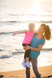 Healthy mother and baby girl pointing while on beach in the even