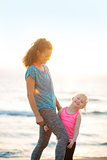 Healthy mother and baby girl on beach in the evening