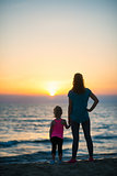 Silhouette of mother and baby girl on beach looking into distanc