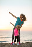 Healthy mother and baby girl on beach in the evening pointing