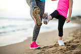 Closeup on healthy mother and baby girl workout on beach in the