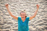 Portrait of fitness young woman rejoicing on beach