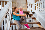 Healthy mother and baby girl sitting on stairs of beach house