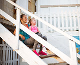 Healthy mother and baby girl sitting on stairs of beach house an
