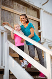 Healthy mother and baby girl standing on stairs of beach house
