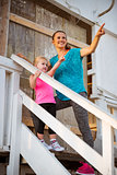 Healthy mother and baby girl standing on stairs of beach house a