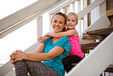 Healthy mother and baby girl hugging on stairs of beach house