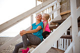 Healthy mother and baby girl kissing on stairs of beach house