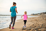 Healthy mother and baby girl running on beach. rear view