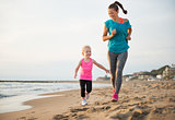 Healthy mother and baby girl running on beach
