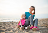 Happy healthy mother and baby girl sitting on beach in the eveni