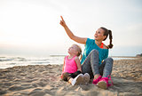 Healthy mother and baby girl sitting on beach in the evening and
