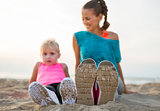 Closeup on legs of fitness mother and baby girl on beach