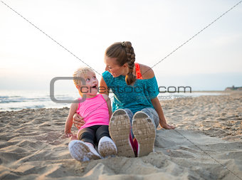 Portrait of fitness mother and surprised baby girl sitting on be