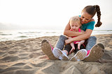 Healthy mother and baby girl hugging on beach in the evening
