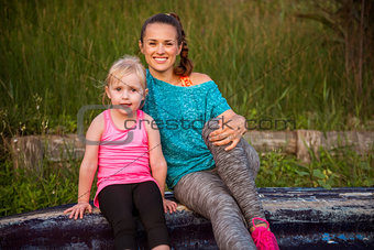 Portrait of healthy mother and baby girl outdoors in the evening