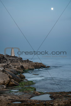 Beautiful rocky cliff landscape with moon over ocean