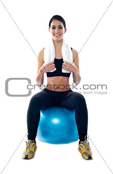 Attractive female athlete sitting on blue ball