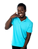 Smiling young man showing calling gesture