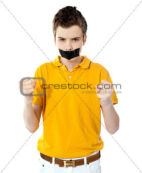 Angry boy with masking tape on mouth.