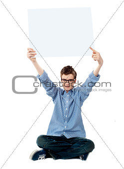 Boy pointing towards white blank billboard