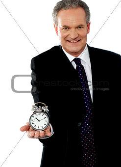 Corporate man showing alarm clock