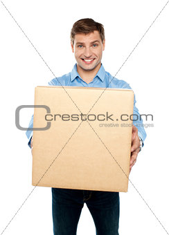 Charming handsome male holding carton