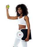 Athlete holding green apple and weighing machine