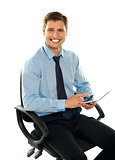 Seated young executive using tablet pc