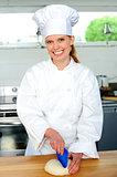 Female chef kneading bread dough