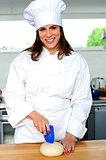 Uniformed female chef in a restaurant kitchen