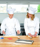 Senior chef teaching newbie female chef