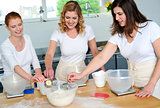 Female chefs team collecting flour from bowl
