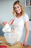 Smiling woman pouring water in flour bowl