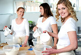 Female bakers pouring water into a plastic bowl