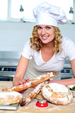 Cheerful female cook posing in kitchen