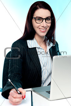 Corporate lady posing with pen in hand