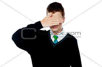 Boy hiding his face and eyes with hand
