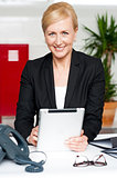Cheerful businesswoman holding tablet pc