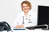Smiling middle aged female doctor sitting in clinic