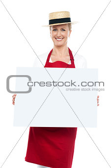Portrait of female chef in hat with blank ad board