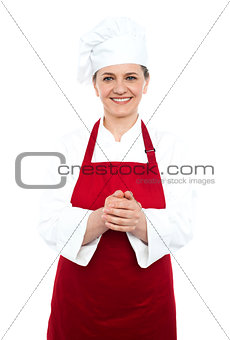 Smiling aged cook standing in red uniform